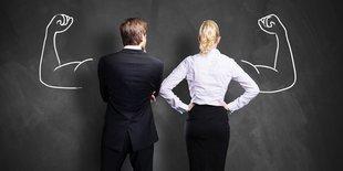 Geschäftsfrau und Geschäftsmann stehen vor einer Wand und recken angezeichnete muskulöse Oberarme in die Höhe