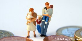 Miniaturfamilie mit Kindern auf dem Arm vor Geldmünzen