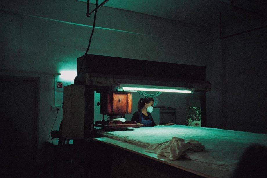 Näherin mit Maske vor großer Maschine mit Textilien / Stoffen