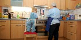 Großmutter und Enkelkind zusammen am Herd in der Küche