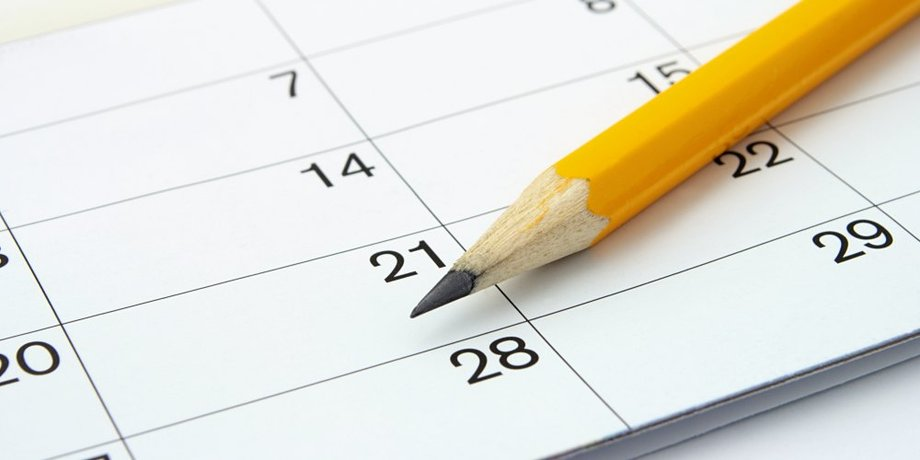 Gelber Bleistift mit Kalender im Hintergrund
