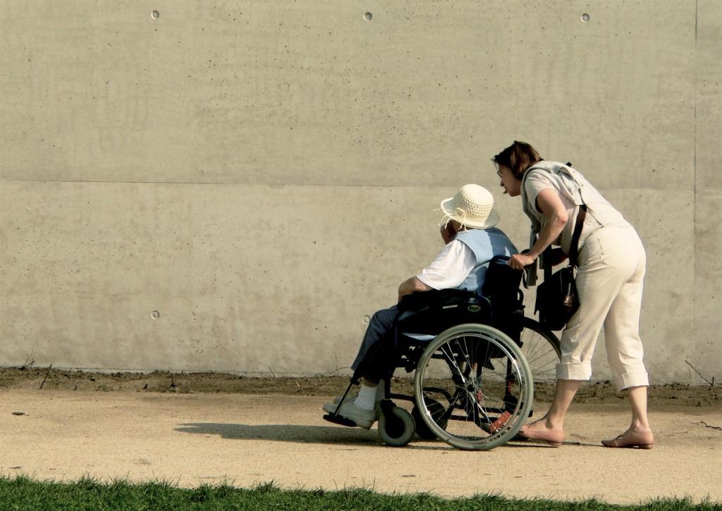 Zwei Frauen, eine im Rollstuhl, eine andere schiebt