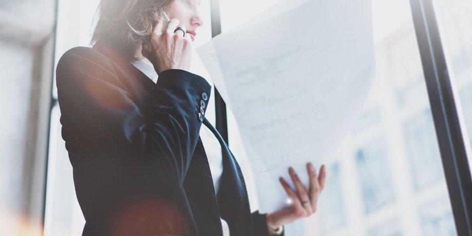 Geschäftfrau mit Unterlagen und Telefon